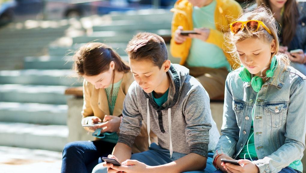 Три подростка сидят на улице и смотрят в свои смартфоны