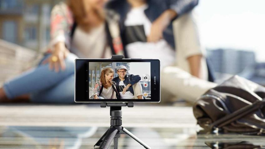 На заднем плане сидит обнимающаяся пара, а на пареднем стоит телефон в штативе и снимает пару на видео