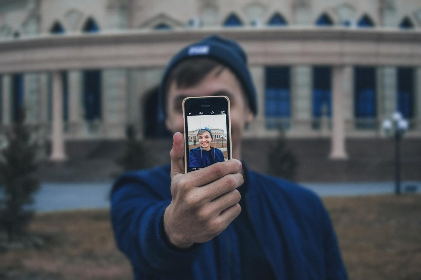 Парень держит в вытянутой руке телефон и снимает себя