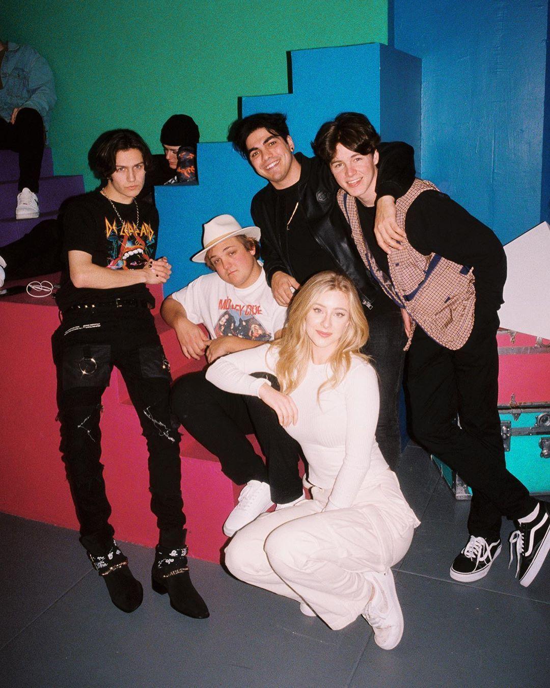 Пятеро молодых людей в чёрной и белой одежде стоят на фоне разноцветной стены