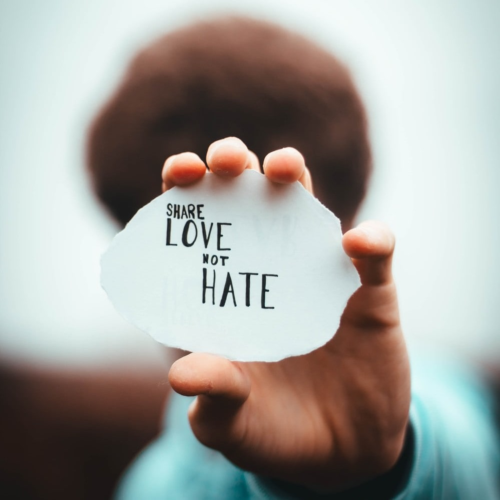 Человек держит в руке клочок бумаги, на котором на английском написано ДЕЛИТЕСЬ ЛЮБОВЬЮ, А НЕ НЕНАВИСТЬЮ
