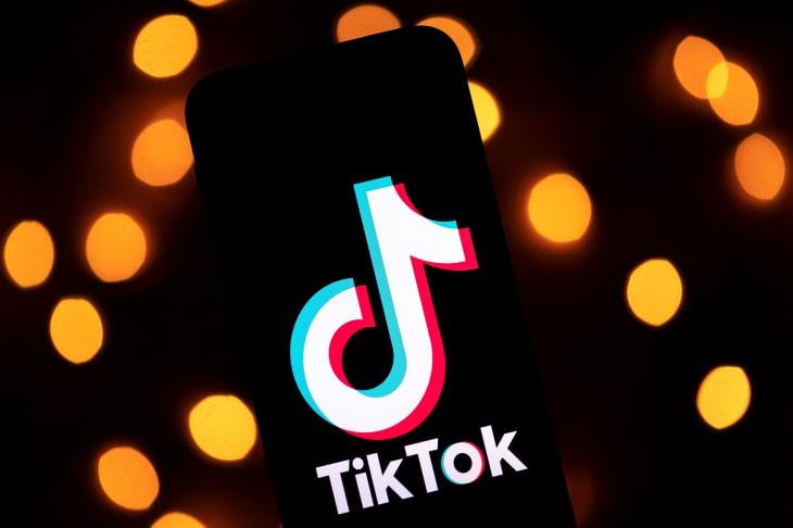 Логотип ТикТок на фоне оранжевых лампочек
