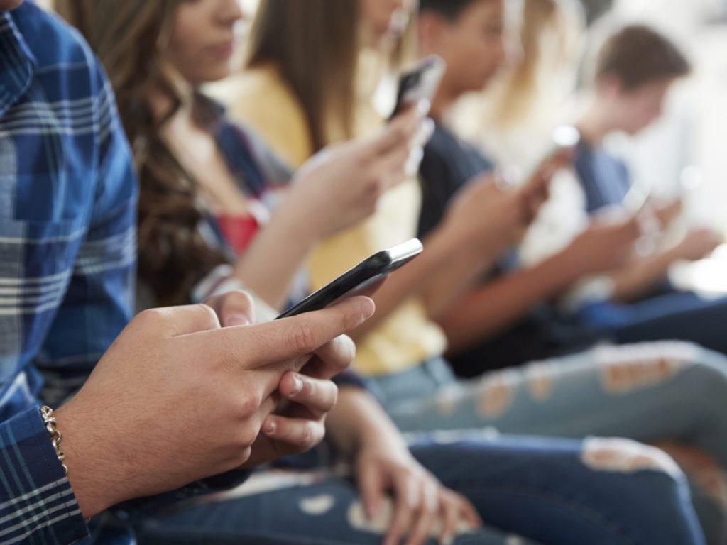 Подростки сидят с телефонами в руках