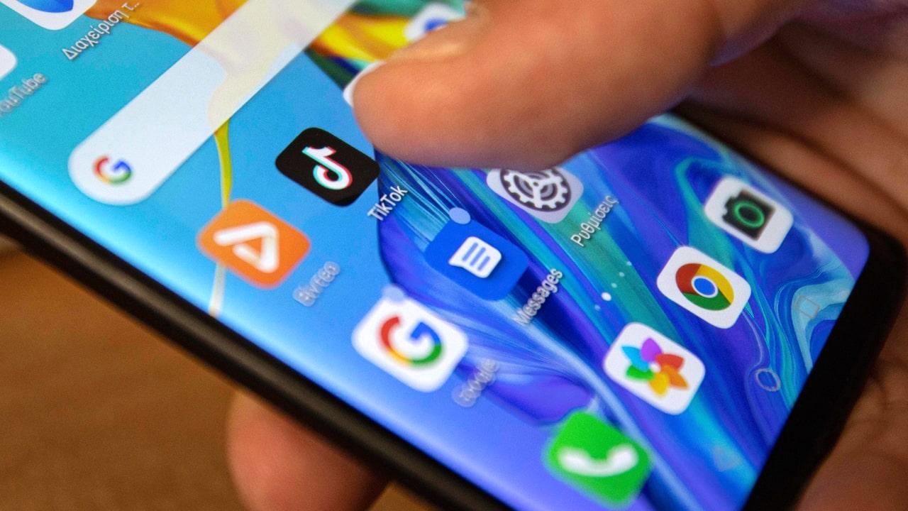 Рука держит смартфон, на котором видны иконки социальных сетей