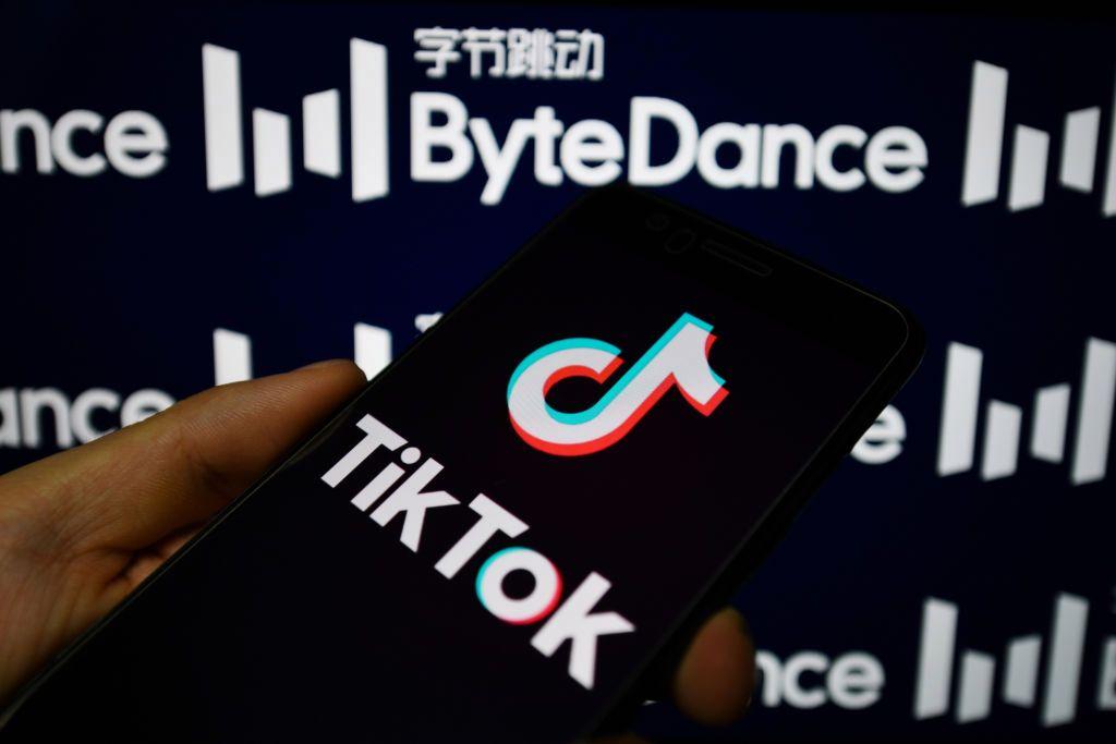 Рука на чёрно-белом фоне держит телефон с лого ТикТок
