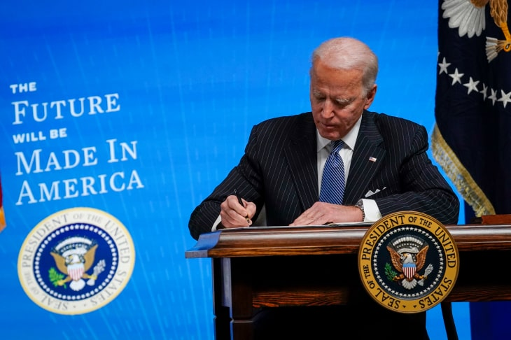 Пожилой человек стоит у трибуны на синем фоне и что-то пишет